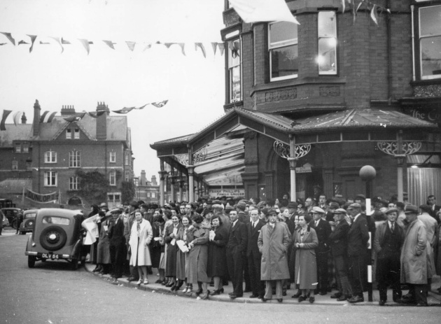 Photo of the throngs of spectators the ISDT attracted to Llandrindod Wells each year. Here crowds gather near the start finish where  Hraham Walker, editor of Motor Cycling and father of Murray Walker Famous for his F1 sports commentaries announces on the arrival of riders. ISDT 1938
