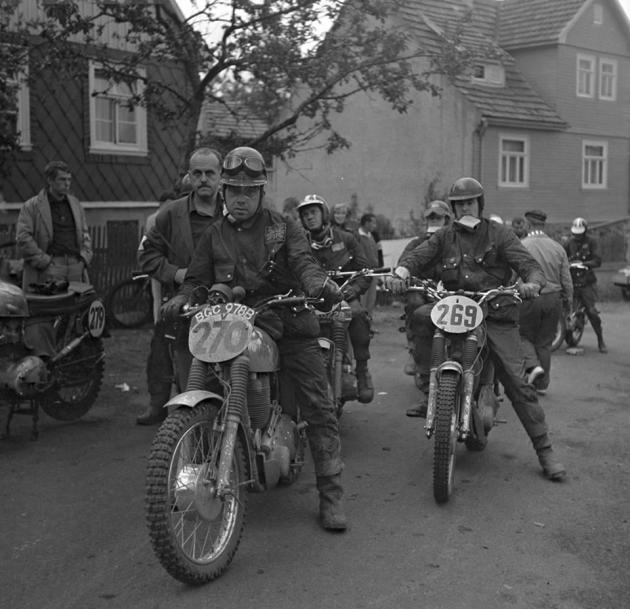 Photo Riders at unknown time check a trio of British riders include #270 Arthur Bates AJS 550 [BGC 978 B] of the GB Silver Vase 'B' Team #269 AS Jones Matchless 584 #279 Ken Heanes Triumph 649 behind Arthur staring into the sky is #278 Steve McQueen