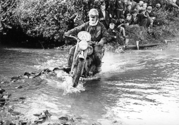Photo - #253 Bob Ray crosses a ford whilst onlooked by a large crowd of young spectators ISDT 1955