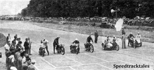 Photo - The Britain v Germany race begins. On the right is the smoke from the maroon. Note how No 193 J Stelzer (BMW) has been caught with both hands in the air, adjusting his goggles while the remainder are in the act of starting up and getting under way. The Trophy team men  (left to right are Stelzer, VN Brittain (Norton) G meier (BMW) GE Rowley (AJS) L Kraus (BMW sc) and WS Waycott (Velocette sc) ISDT 1937 (Speedtracktales Collection)