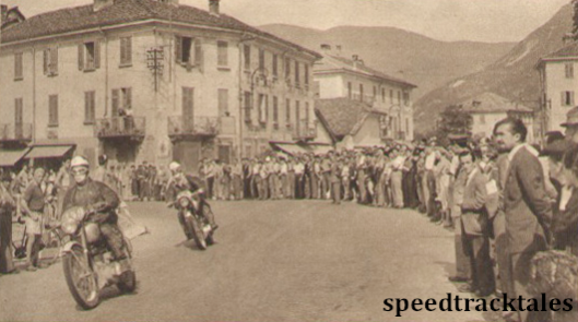 Photo - Shirt-sleeved crods at Gravellona watch the ISDT competitors come though. L Archer (BSA) is ahead of E. Dow (BSA) ISDT 1951 (speedtracktales archive)