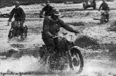 Photo- Four British riders splash across the waters of the River Isar, in desolate country. Trophy man #7 Tim Gibbes (AJS) is leading, followed by privateer #8 Eric Chilton (Triumph), Silver Vase teamster #11 Vic Eastwood (AJS) and top-scoring Trophy member #10 Johnny Giles (Triumph) ISDT 1962 (Speedtracktales Collection)