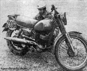 Photo - Back at the Garmisch-Partenkirchen ski-stadium used as a 'parc-ferme,' Soviet rider #206 Nicolaj Kulev gives his hefty 175cc Russian two-stroke a quick tune-up after a first day of torrential rain. ISDT 1962 (Speedtracktales Collection)