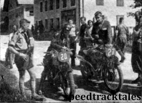 Photo - #27 Len Heath (497 Ariel) and #20 HN Toomey (498 Panther), the latter disguised by a crash helmet have a few moments to enjoy the sunshine and a cigarette while waiting their turn to enter the check. ISDT 1939 (Speedtracktales Archive)
