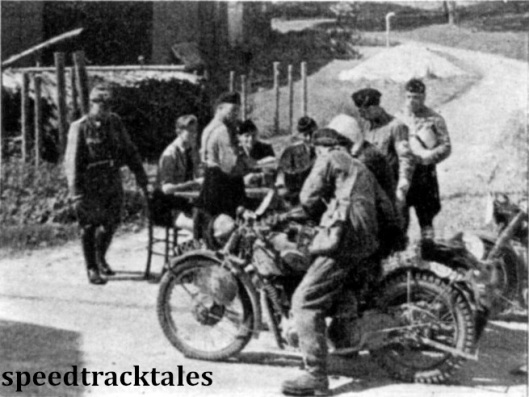 Photo - A typical scene at a check with Nazi's operating the control and a policement looking on #6 is Capt GM Barry of the British Army Norton Team. ISDT 1939 (Speedtracktales Archive)