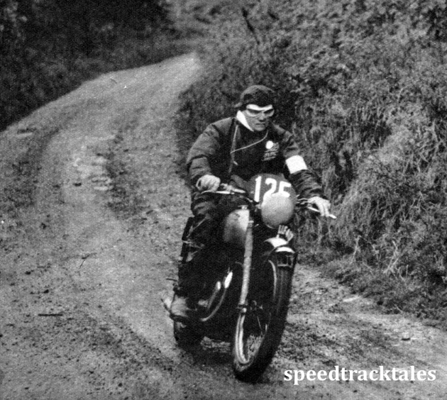 Photo - Two fingers on the clutch lever one on the front brake control, #125 Hugh Viney (347 AJS), member of the British Trophy team, looks seriously purposeful. Later he took a mild toss owing to a fallen competitor. ISDT 1950 (Speedtracktales Archive)