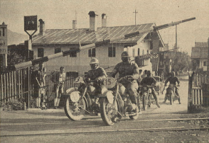 Photo – The railway crossing gates were such thing. Again and yet again, they were closed when riders did arrive. But, there always were attendants, so that lost time could be credited, if necessary. The pictured riders are: #13 Oberfeldwebel [staff sergeant] Linhardt on BMW R 51. #15 Oberwachtmeister [staff sergeant] Höser (his clutch lever is still o.k!) from the Kraftfahrtschule der Luftwaffe [Air Force motoring school] on BMW R 51, #16 Brunetto on 500cc Sertum, and from Holland #18 C. A. Ridders on BMW R 51. ISDT 1939 (das Motorrad)