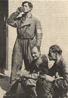 Photo It had been quite hot during the six days trial. Here one can see three thirsty souls as they refill some liquid. The tall one, standing at the outside, is the Swede Hedelin, sitting in the middle is Pierre van Maldeghem, president of the Belgian motorcycle association, and on the right hand side, our [Motorrad magazines] employee Heinz Hahmeyer. ISDT 1939 (das Motorrad)