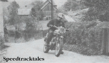 Photo - Bend-swinging his Triumph through Altaussee on the Wednesday, Ken Heanes drops a precautionary foot as the back wheel steps out ISDT 1960