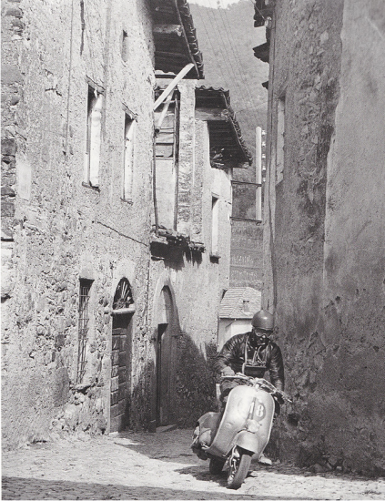 Photo of Scooter Rider passing through narrow streets in a town ISDT 1951