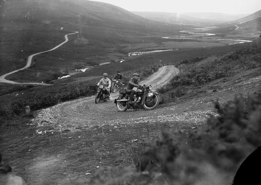 Photo by P B Abery titled 'Motorcycle racing in Rhayader on the old road to Aberystwyth'. The image may be from the ISDT 1933 with riders #124 A P Van Hamersveld 499cc Rudge Holland - Rtd #128 J Moejas 597cc Ariel Holland - Silver #129 H Kelly 497cc Ariel GB - Rtd. (Image Courtesy of the P B Abery Collection, National Library of Wales)