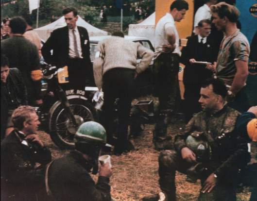 Photo. The US team often shared their time with British Riders. In this photo Steve McQueen is sitting with some green helmeted Brits, one of whom is Arthur Bates who is from Rhayader in Mid Wales and part of a dynastic family who have done much to promote the sport. Arthur was for many years the Clerk of Course for the Welsh Two Day Trial ISDT 1964