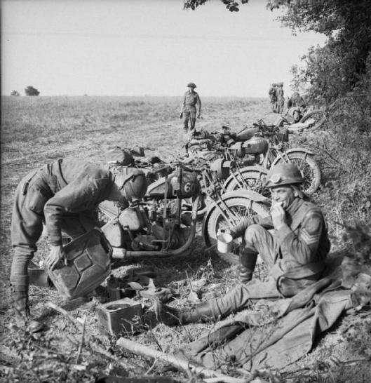 Photo - Sgt J Lloyd (right) and L/Cpl Jones, two motorcycle despatch riders of the Royal Welsh Fusiliers have a 'brew' before the attack on Evrecy, 16 July 1944. (Image courtesy Imperial War Museum)