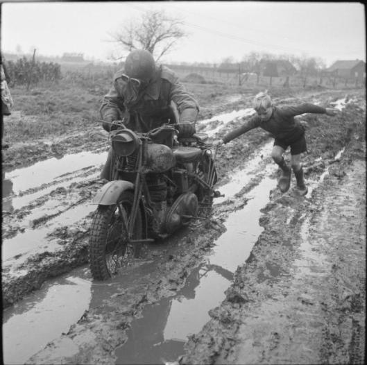 Photo - A small boy helps a motorcycle despatch rider negotiate a muddy road in Holland, 11 December 1944. (Image courtesy Imperial War Museum)