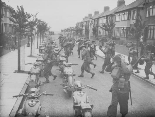 Photo - A 'fighting column' from the South Wales Borderers man their motorcycles which are parked in a suburban street in Bootle, Liverpool, England, 16 August 1940. This training operation formed part of British preparations to repel the threatened German... (Image courtesy Imperial War Museum)