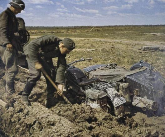 Photo - German despatch riders dig out their Zundapp motorbike which is bogged down in mud on the Eastern Front probably during the Spring thaw. (Image courtesy Imperial War Museum)