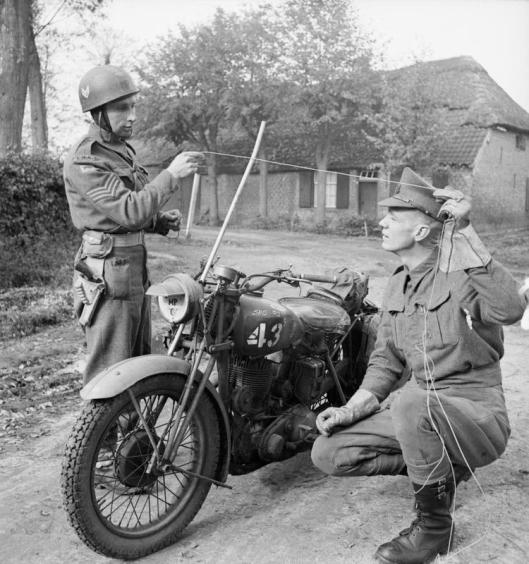 Photo - Corps of Military Police motorcyclists demonstrate how a metal rod fitted to a motorcycle can prevent the rider from being killed by a wire stretched across the road, 25 October 1944. (Image courtesy Imperial War Museum)