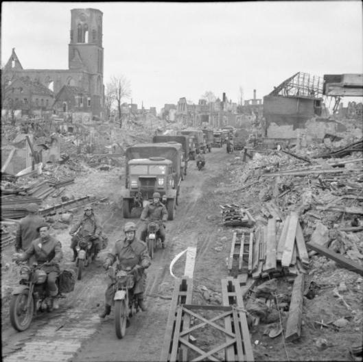 Photo - Trucks and motorcycles pass through Stadtlohn, 1 April 1945. (Image courtesy Imperial War Museum)