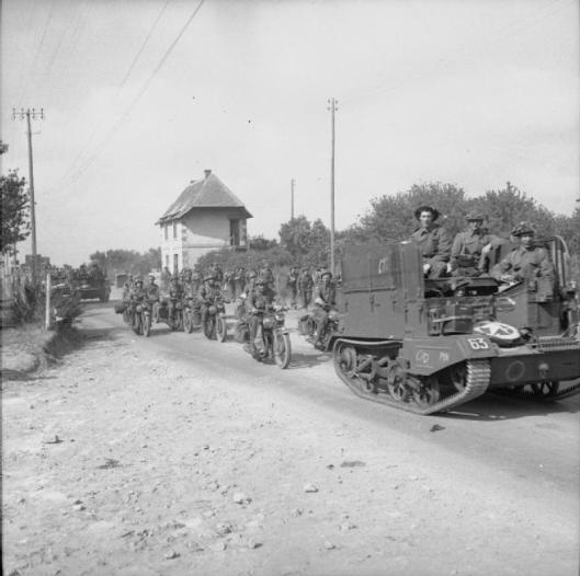 Photo - Universal carriers and motorcycles driving inland from Arromanches during the build-up of Allied reinforcements in the bridgehead, 22 June 1944. (Image courtesy Imperial War Museum)