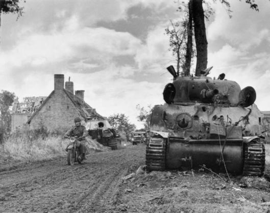 Photo - A motorcycle despatch rider passes a knocked-out Sherman tank and behind, a German Panther at Fontenay-le-Pesnel, 27 June 1944. (Image courtesy Imperial War Museum)