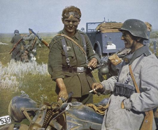 Photo - Two dust covered German despatch riders relax with cigarettes by their Zundapp motorbike after delivering a despatch on the Eastern Front. (Image courtesy Imperial War Museum)