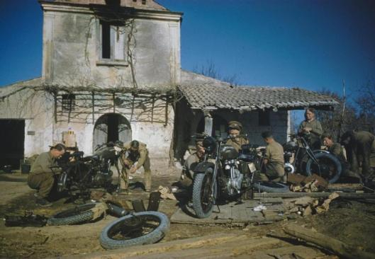 Photo -  Motorcycles being assembled at a forward REME workshop by the 56 Infantry Troop Recovery Unit, Royal Electrical and Mechanical Engineers. (Image courtesy Imperial War Museum)