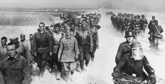 Photo - German motorcycle troops and infantry pass a long column of Russian prisoners during the advance into the Soviet Union, 1941. (Image courtesy Imperial War Museum)