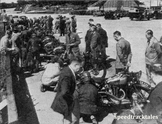 image - Great activity - but not feverish activity - in the tube changlng tests, which were held at Brooklands. Nearly everyone In the picture is a well-known personality in motorcycle circles (speedtracktales collection)