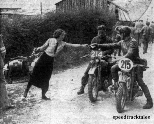 Photo - An einer Kontrolle des 2. Fahrtages. Der deitsche Zündappfahrer Schäfer (nr 215) gibt gerade seine Kontrollkarte zum Stempeln ab. Links neben ihm der englische BSA-fahrer Cartwright ISDT 1937 (Speedtracktales Collection)