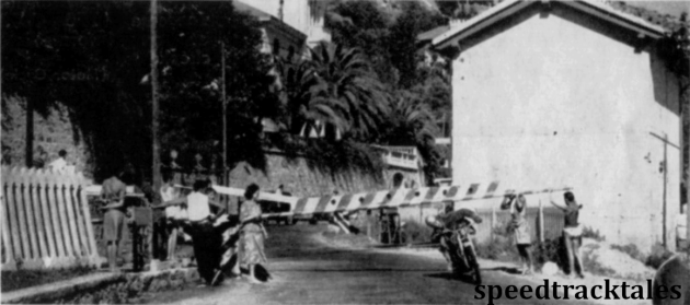 Photo - A competitor ducks under a barrier at a level crossing on the main Genoa line. Competitors were helped in this way whilst normal traffic was held up. ISDT 1949 (Speedtracktales archive)