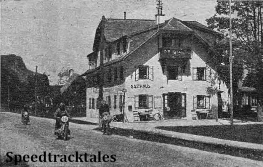 photo - The Italian E Catolini (Guzzi) following F. Mayer (BMW) in Wolfgang on the second day. The picturesque hotel, with overhanging eaves, is typical of the district. ISDT 1939 (Speedtracktales Collection)