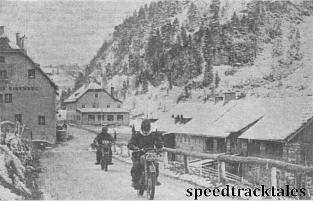 Photo - So this is Austria, in September! The Dutch 499cc BSA rider M.Rodenberg leads Phil Mellers (498 Ariel) through the street of a snow clad village on Saturday. ISDT 1952 (Speedtracktales Collection)