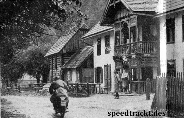 Photo - P Carissoni (124 Rumi), of Italy, passes a picturesque Tyrolean wooden 'music-box' building in admont village. ISDT 1952 (Speedtracktales Collection)