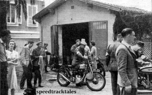 Photo - Charlie Rogers wheels his 346cc Royal Enfield [GWP 369] outside the British riders' depot. Others to be seen are Allen Jeffries, team captain, and Len Heath, team manager. ISDT 1948