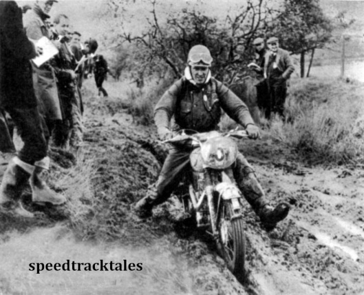 Photo - Before a big crowd, #207 Peter Fletcher (346 Royal enfield) of Briain's Vase 'A' team, footslogs through deep mud on Friday afternoon. ISDT 1961