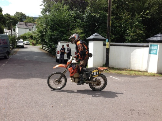 Photo - A rider competing in the Powys Enduro crosses the road from Llanwrin to Machlwyd at Aberangell, part of the route past ISDT's took to reach the Bwlch y Groes which is a couple of miles away