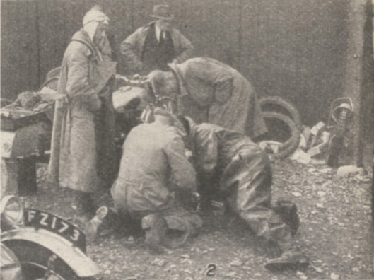 Photo - Trouble with the tyres - a group in a huddle over last minute preparations. At Llandrindod many such scenes were being enacted last week-end just before the competitors were due to present their machines for official scrutiny - ISDT 1938 (image courtesy Morton Media)