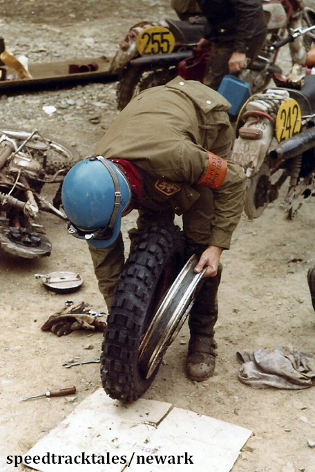 Photo - Gold medal winner #242 J Jasansky of Czechoslovakia at the end of the day fits new boots to his bike ISDT 1971 (Newark Collection)